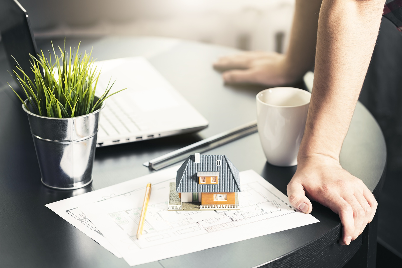 Model house and blueprints on desk