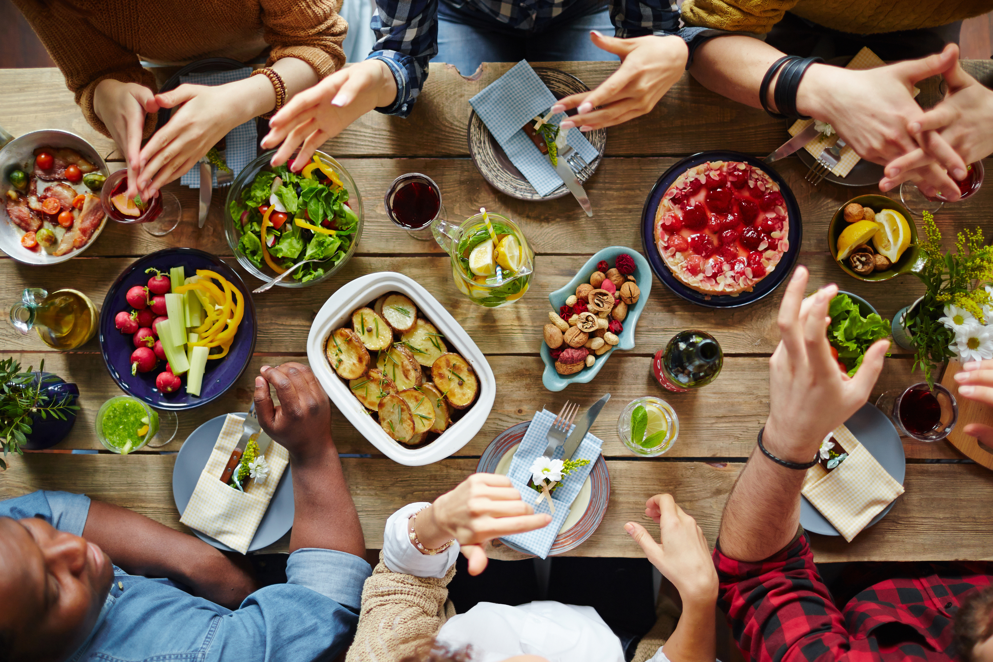 Group of people sitting around a table eating food