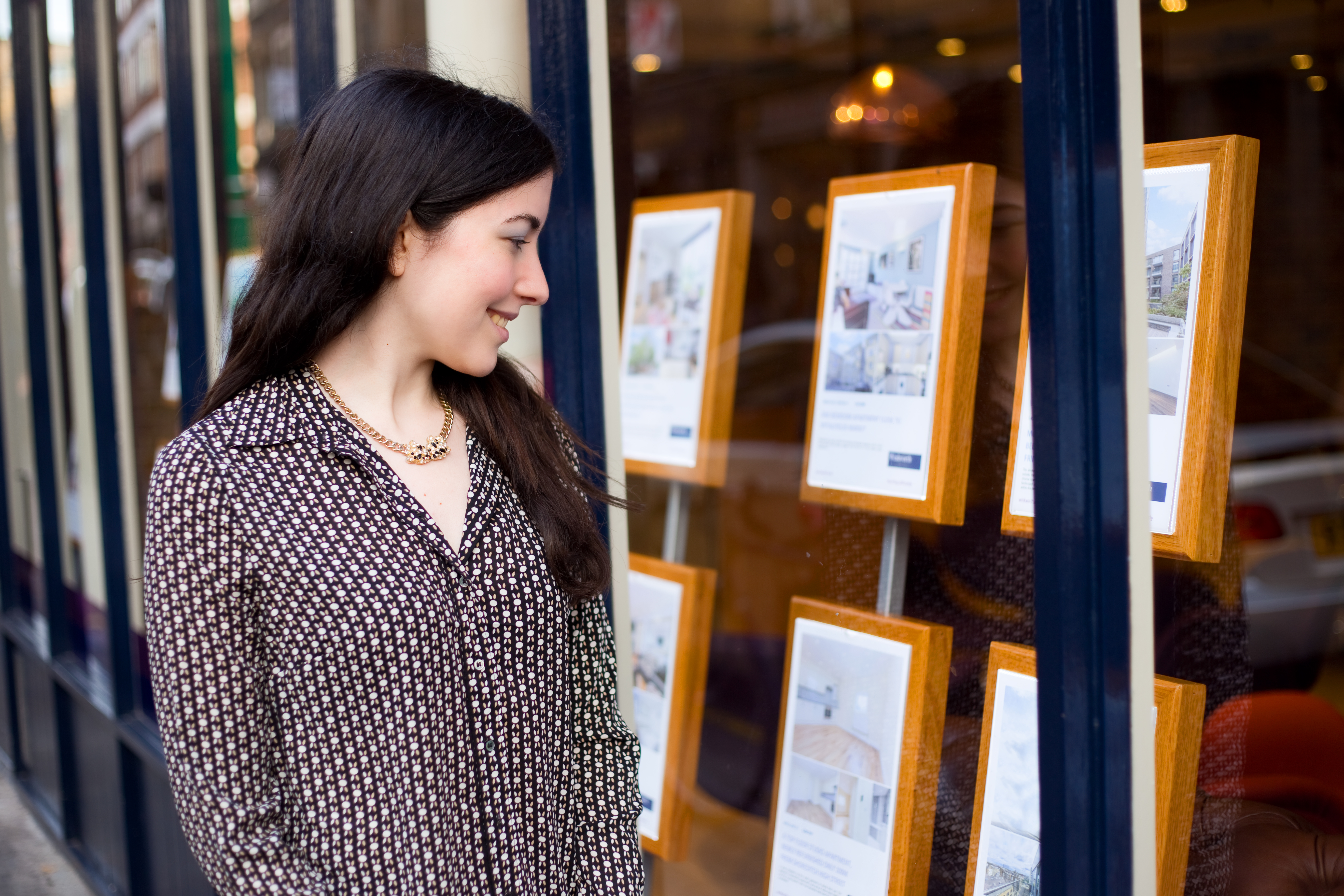 Women looking at real estate in shop window
