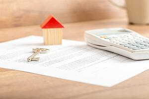 Contract, house keys and calculator on a table